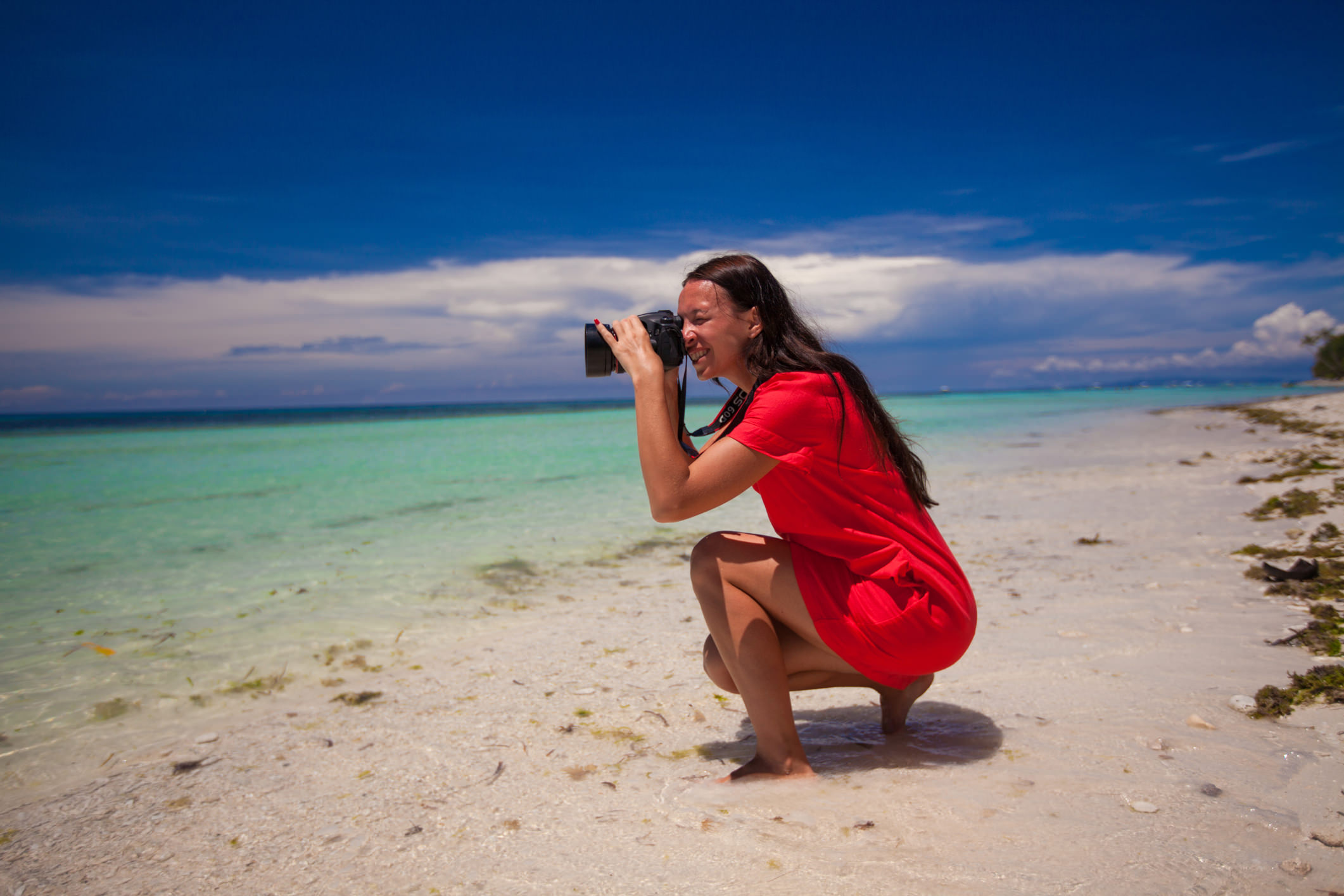 Woman on beach with camera image