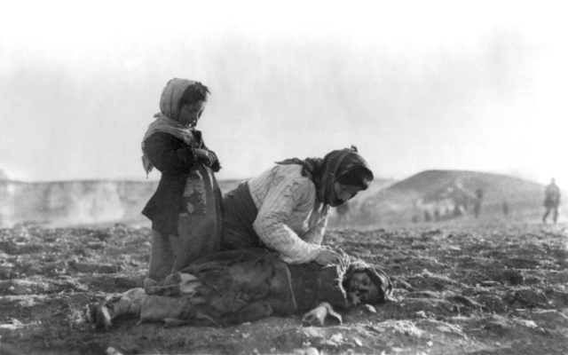 Armenian woman kneeling beside dead child in field image