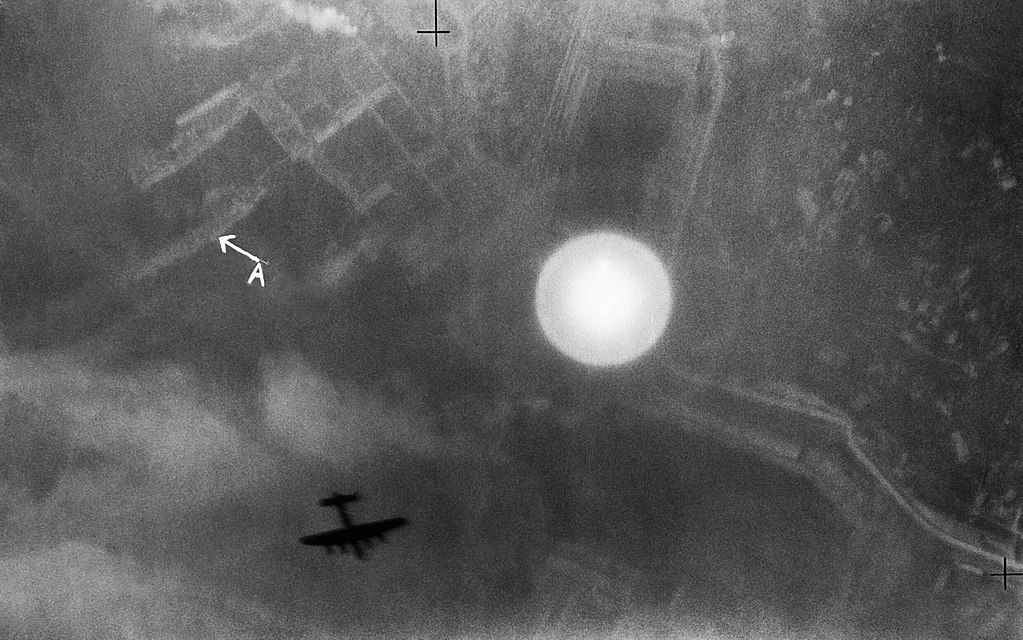 1024px An Avro Lancaster silhouetted over the Italian port of La Spezia on the night of 13 14 April 1943. C3697 image