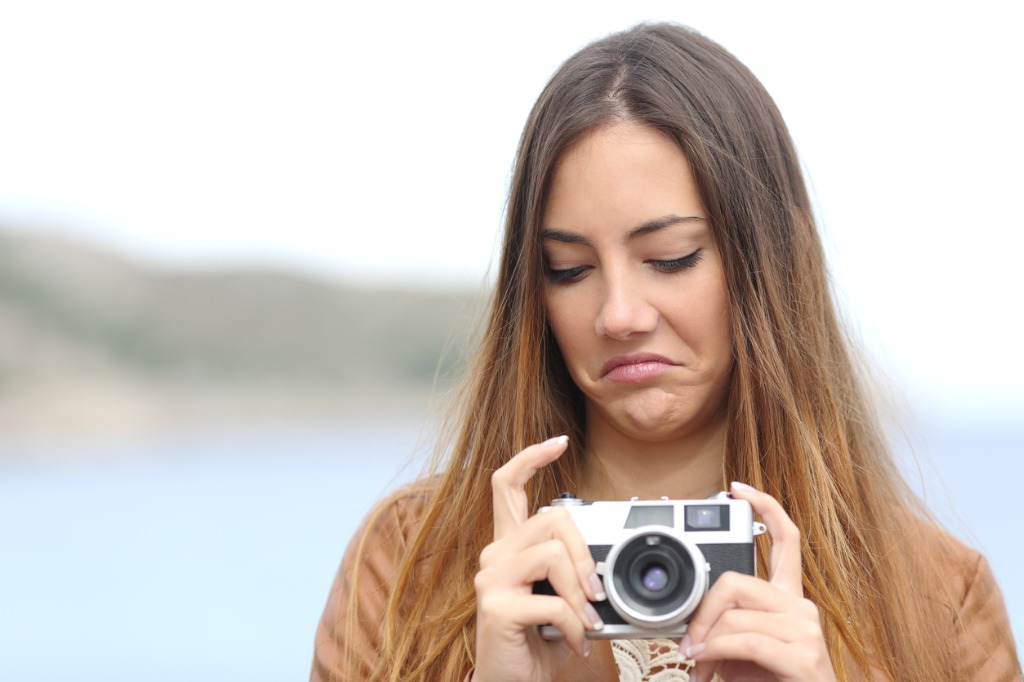 upset woman looking her old slr photo camera picture id492810294 image