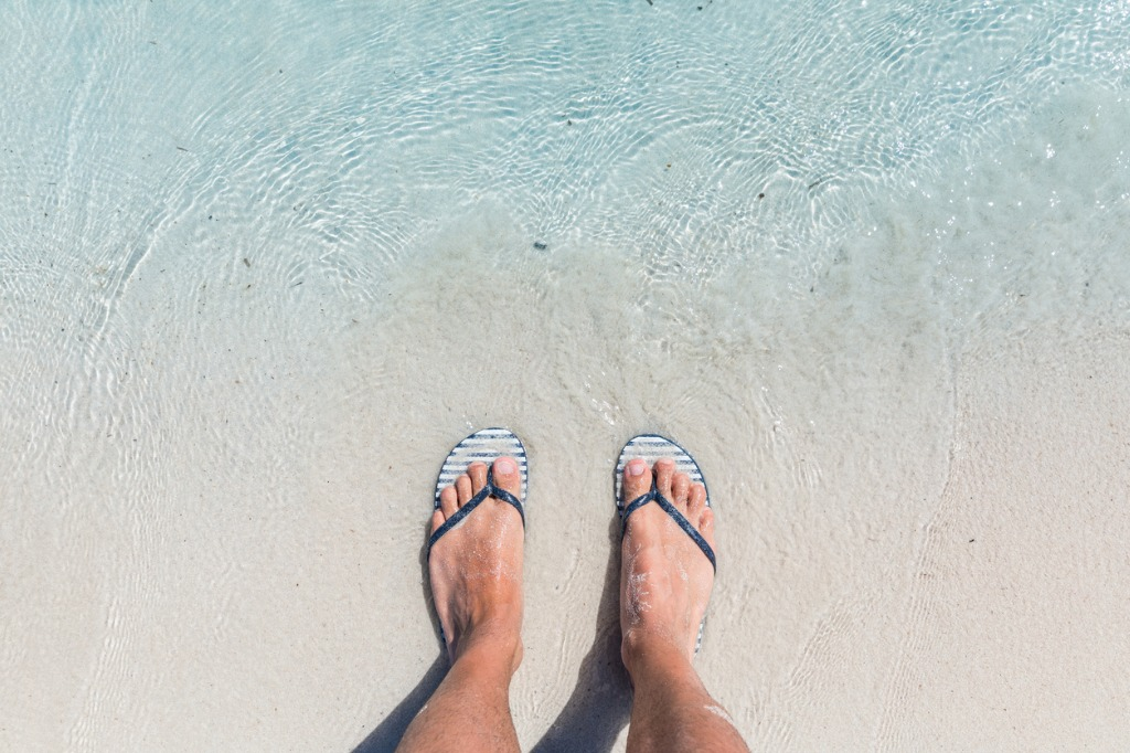 male feet wearing female flip flops at beach picture id648226816 image