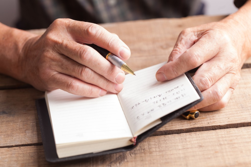 old man writing notes in book picture id652420342 image