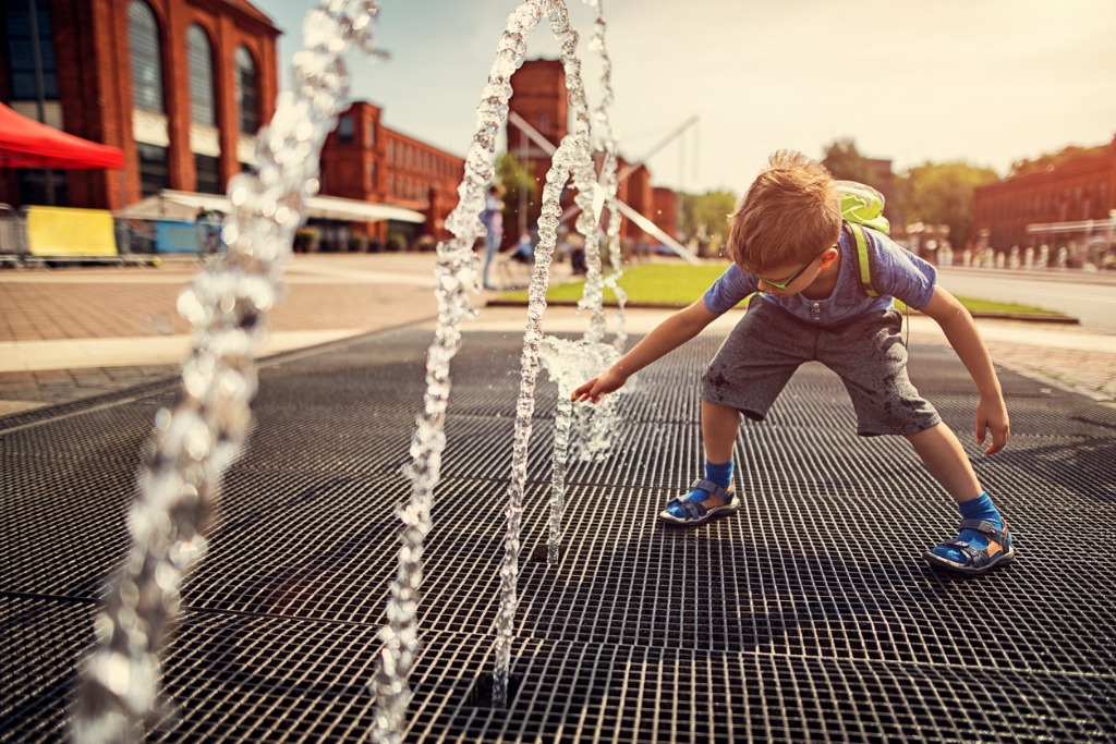 little boy playing with fountain on a hot summer day picture id693436462 image