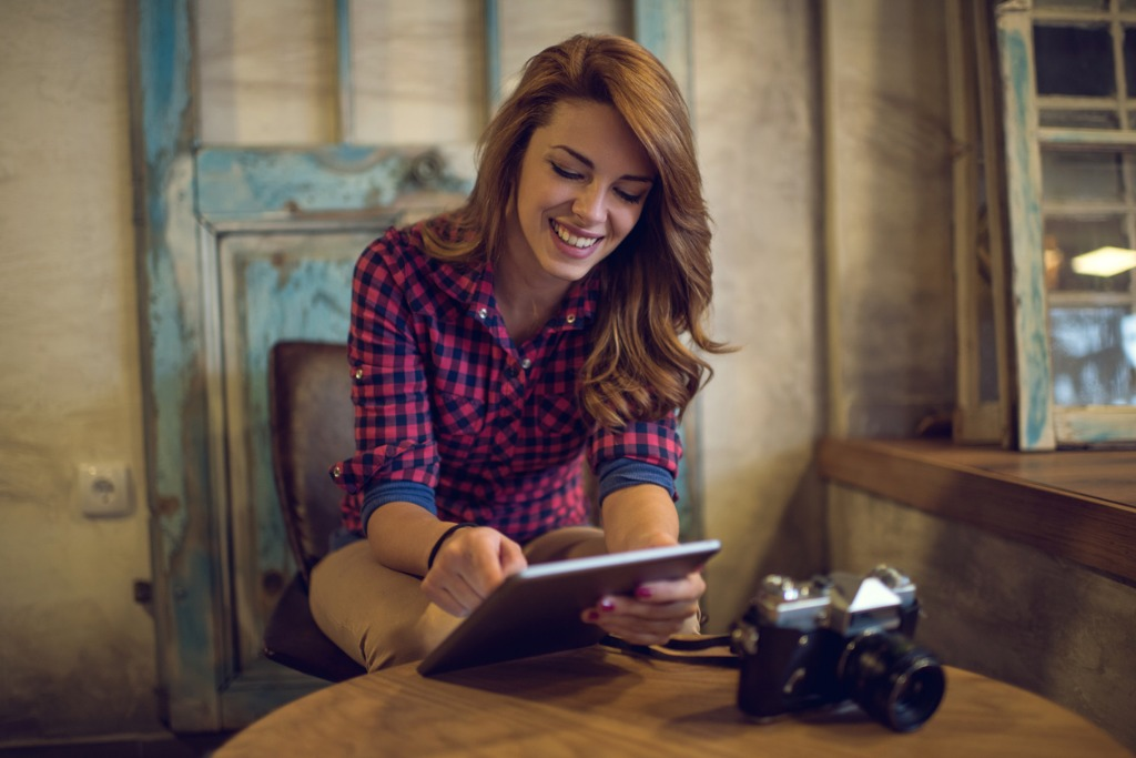 young happy woman reading something from an ereader picture id509194904 image