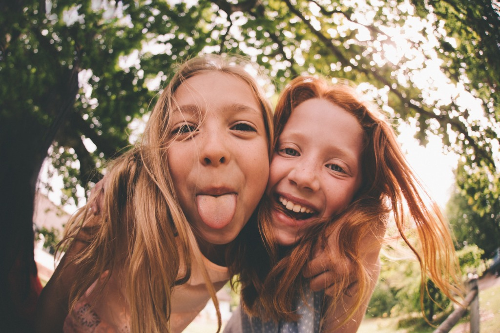 girls laughing and pulling faces at the camera in park picture id518023558 image