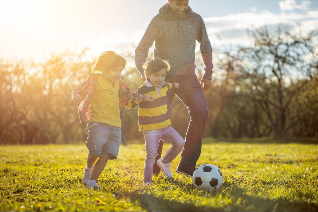 father playing soccer with two sons at the public park at sunset picture id830170424 image