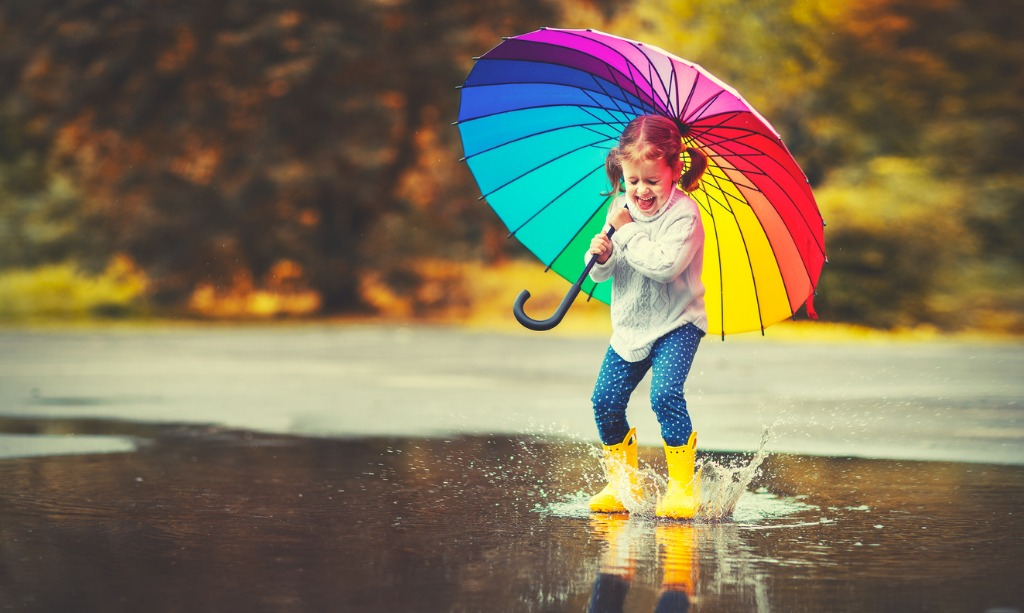 happy funny child girl with umbrella jumping on puddles in rubber picture id840730074 image