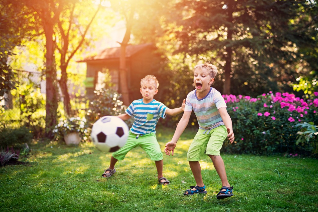 little boys playing football in the garden picture id653447514 image