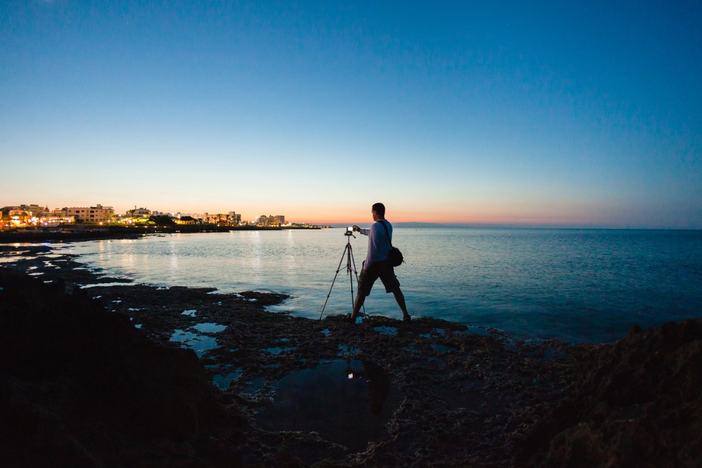 photographer taking a photo of a beautiful sea view picture id694514940 image