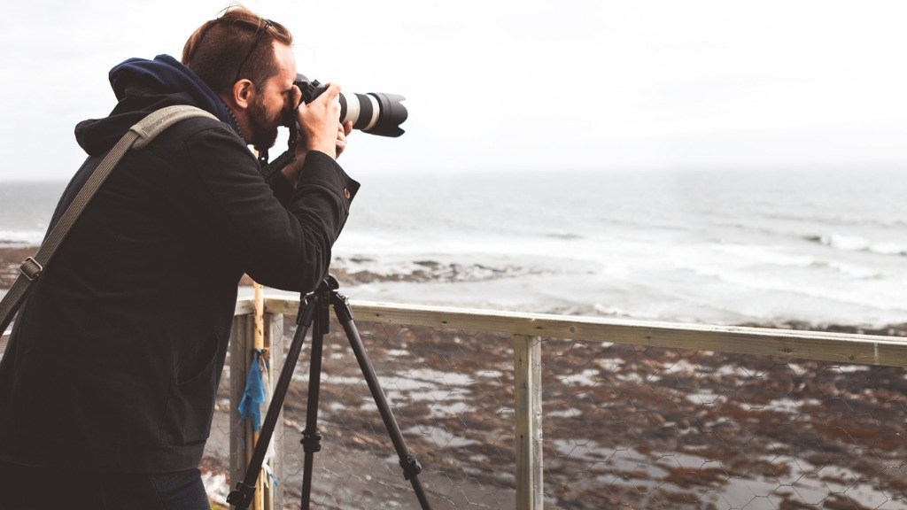young man holding a camera on a tripod and taking a picture of the picture id913121378 image