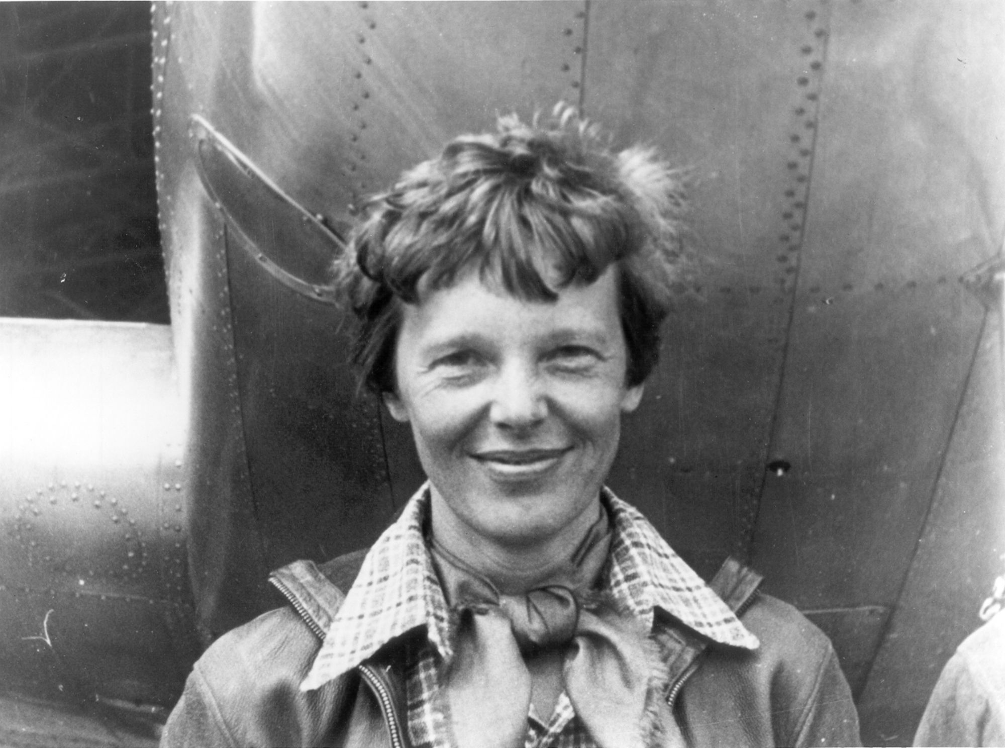 Amelia Earhart standing under nose of her Lockheed Model 10 E Electra small image