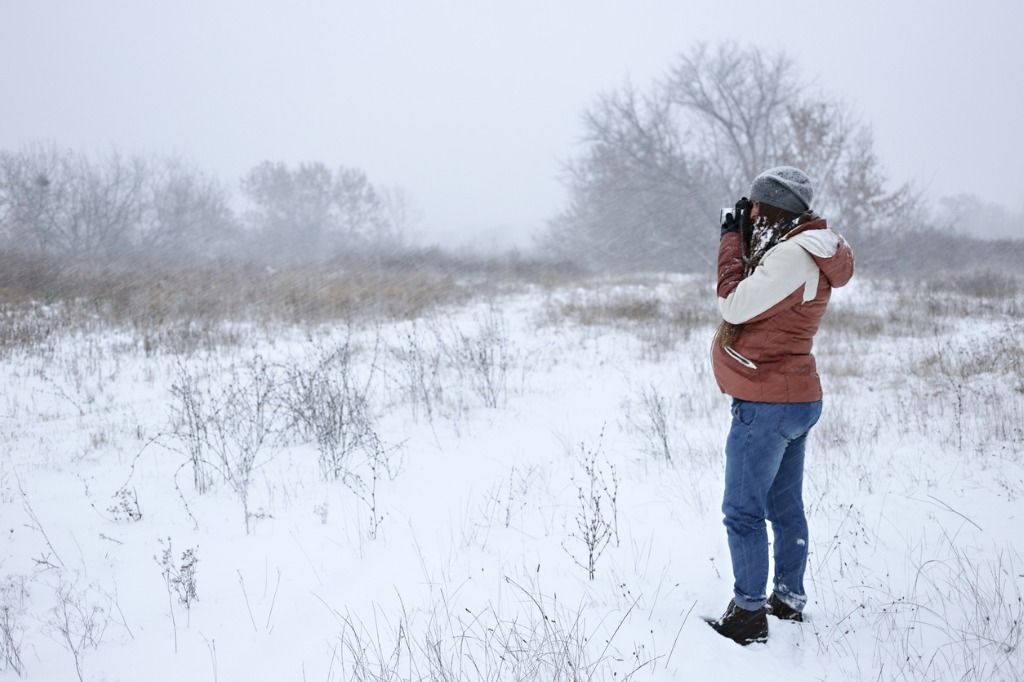 pregnant woman making photo with retro film camera during a blizzard picture id869716878 image
