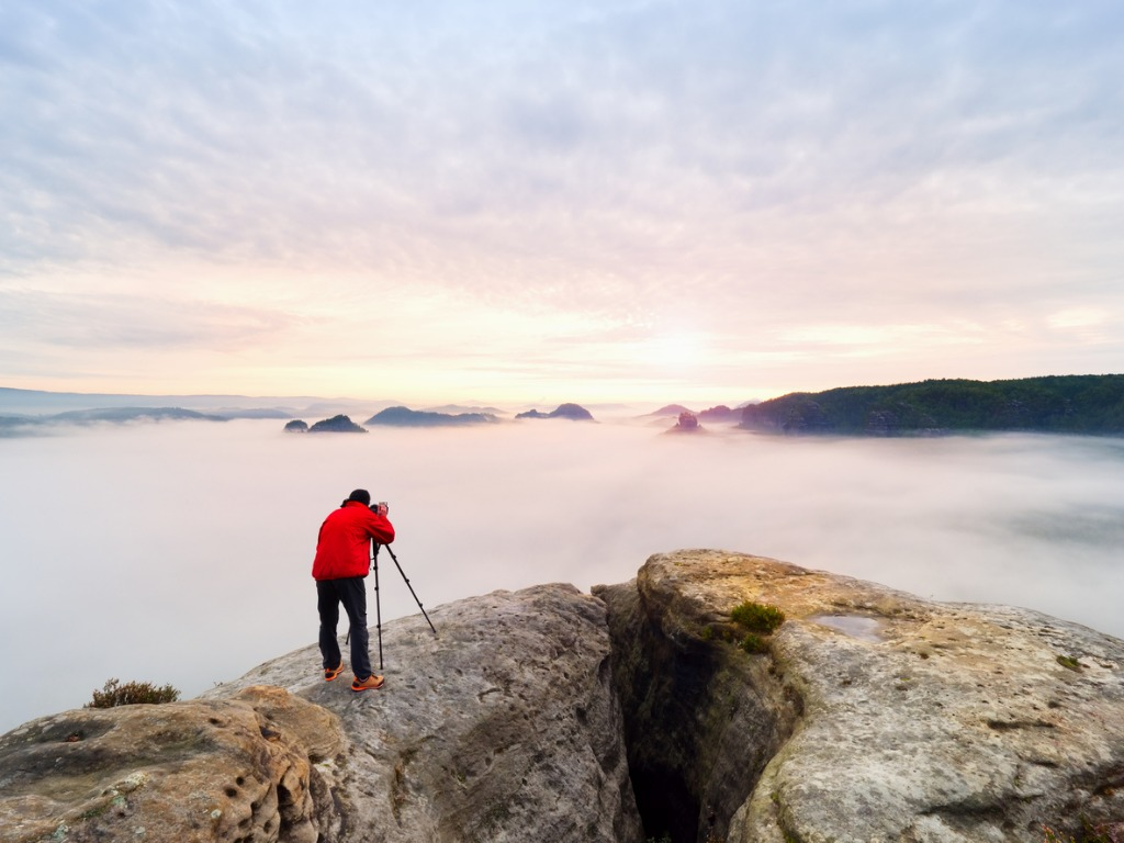 professional photographer above clouds man takes photos with camera picture id924786632 image