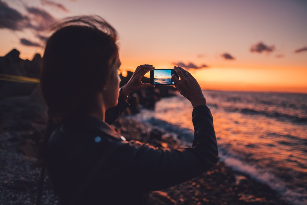 woman at the beach photographing the sunset picture id929516304 image