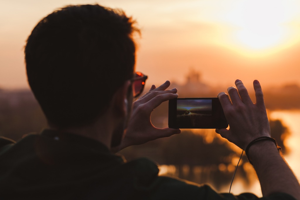 young man taking a picture of the sunset picture id661081678 image
