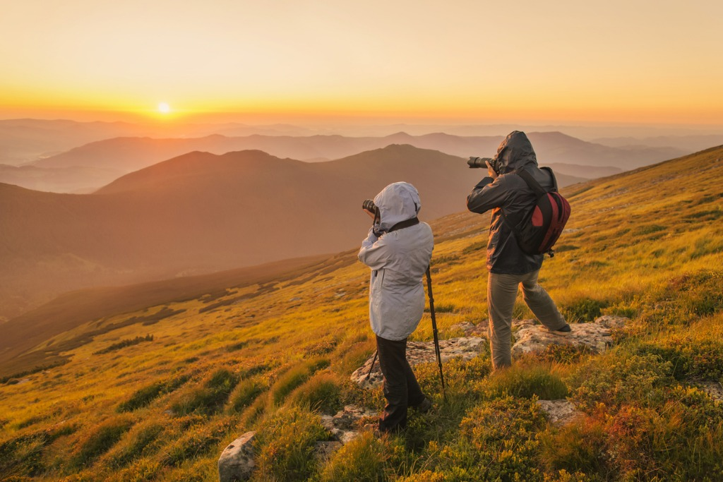 photographers takes a sunset in the mountains picture id484850796 image