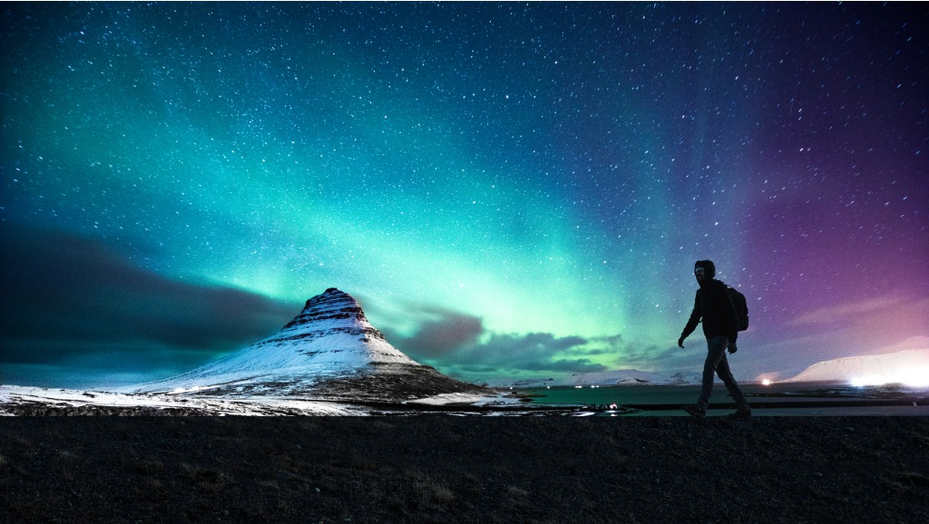 northern lights in mount kirkjufell iceland with a man passing by picture id663261182 image