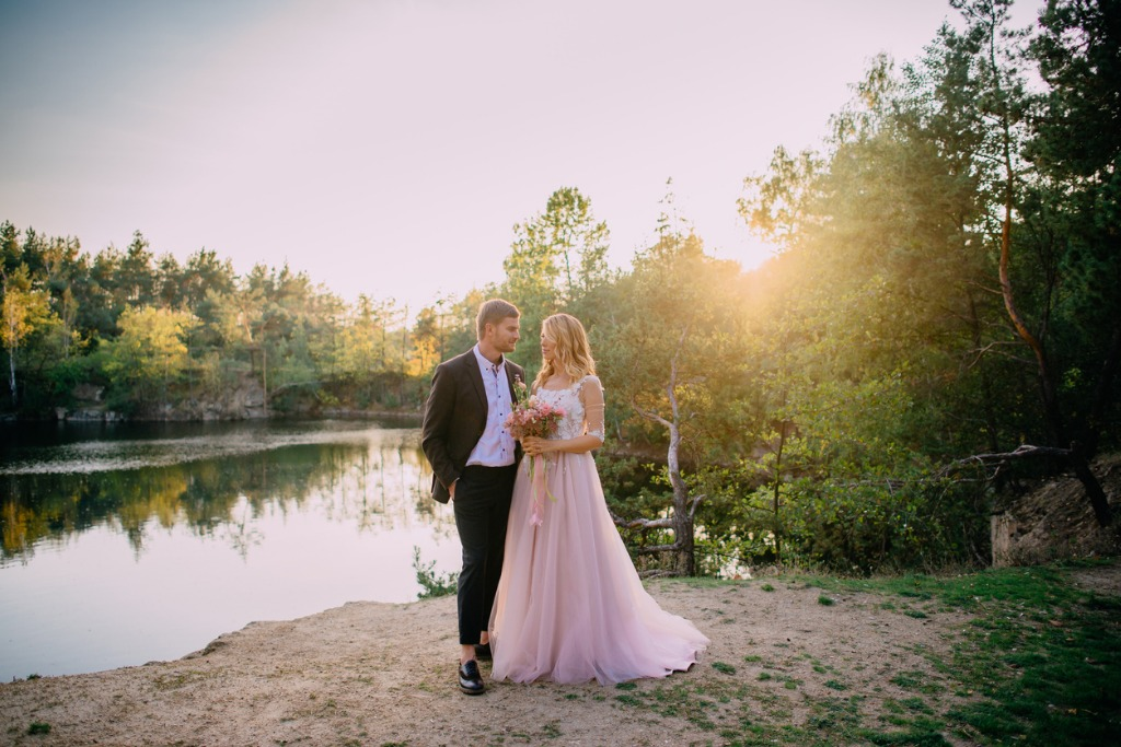 happy newlyweds standing on the lake shore at sunset picture id934862154 image