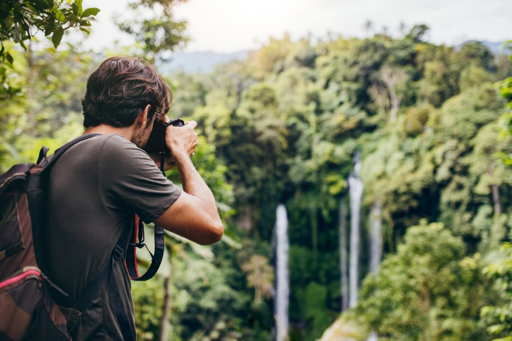 male hiker photographing a waterfall in forest picture id580120812