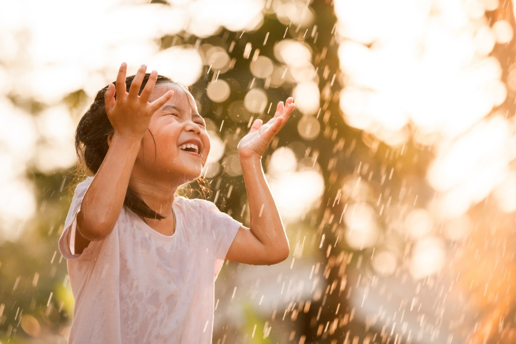 happy asian little girl having fun to play with the rain picture id687863952 image