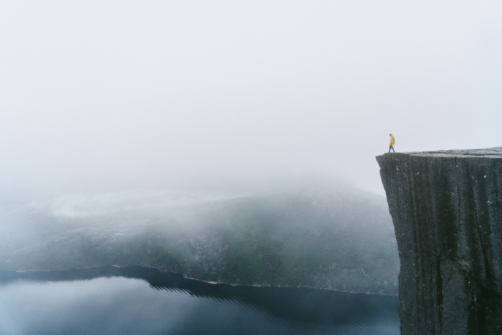 man in yellow raincoat on the preikestolen in fog in norway picture id700678042 image
