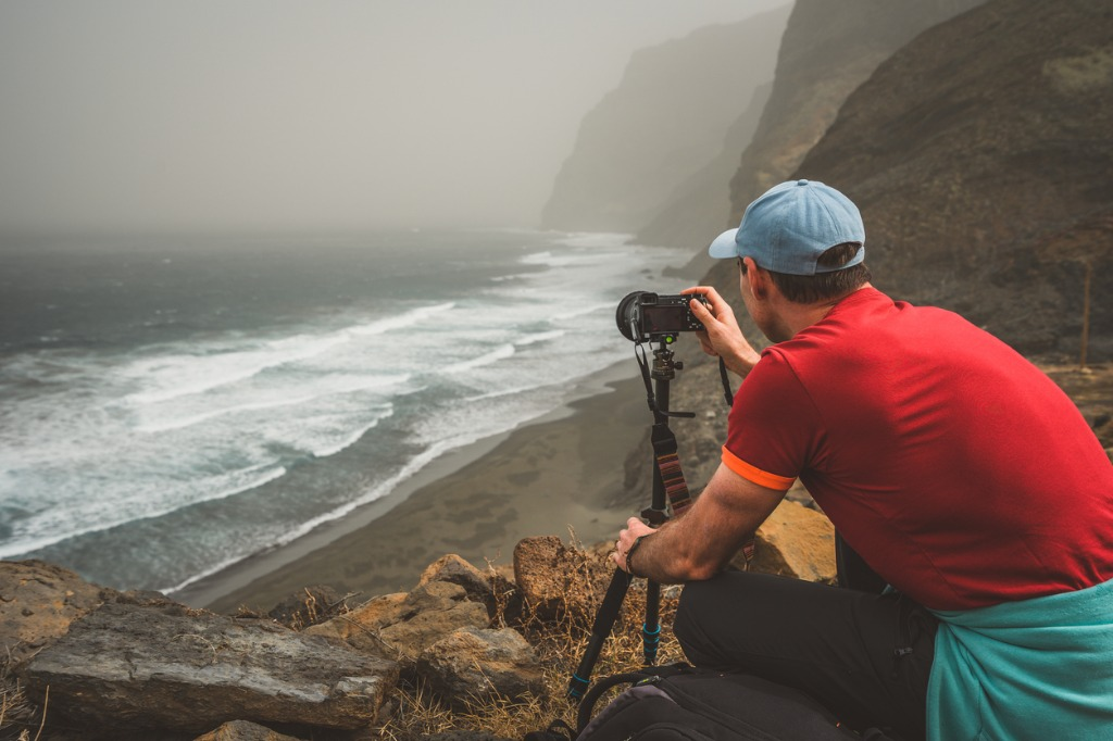 tourist making photograph of cliff coastline with ocean waves from picture id956667234 image