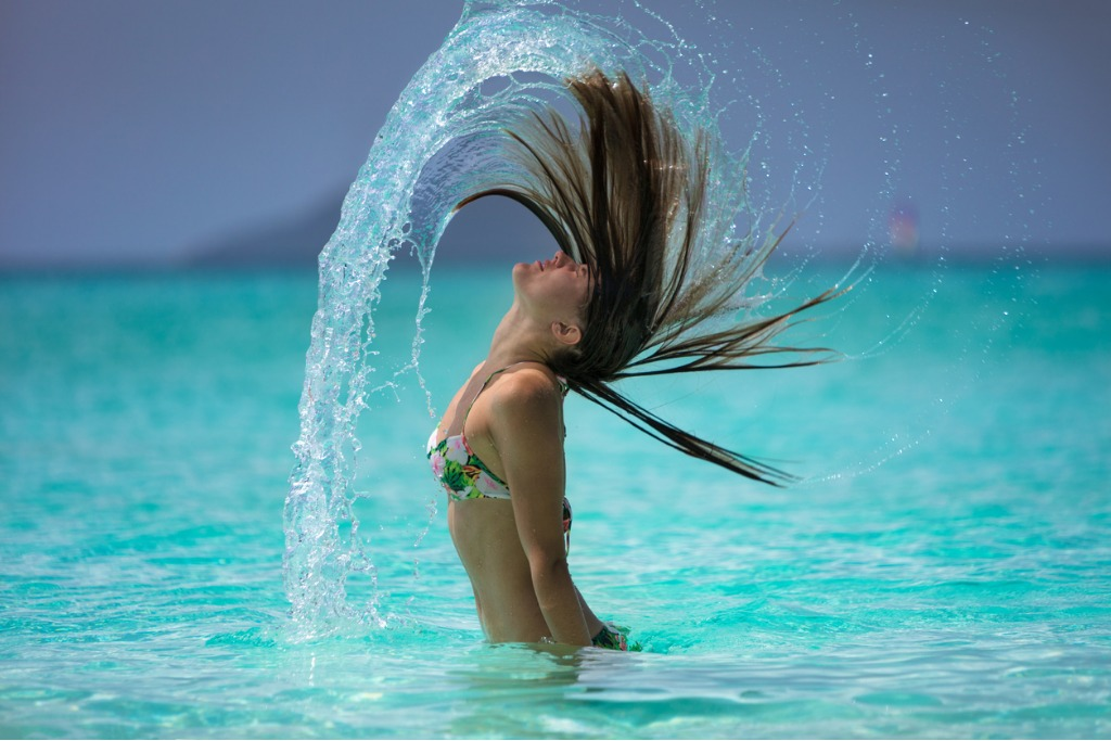 attractive woman flipping hair on a tropical beach in the caribbean picture id839416574 image