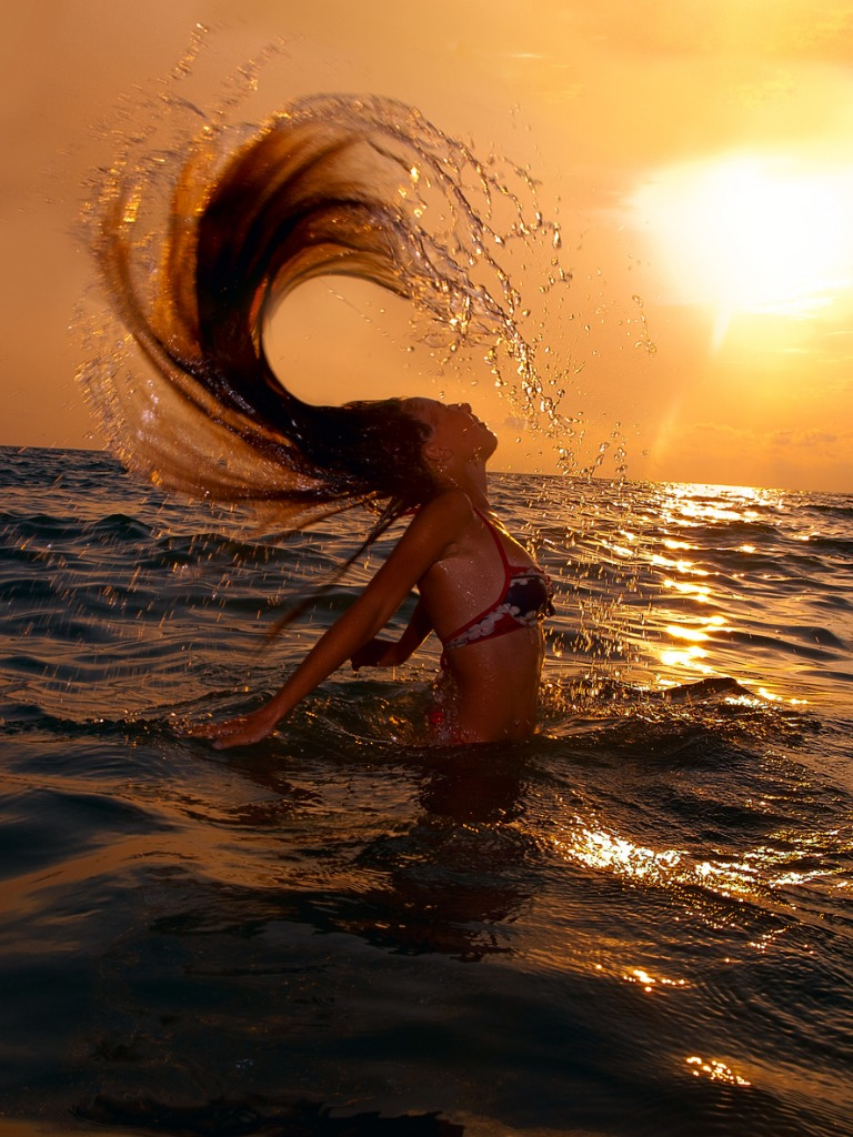 girl in the sea at sunset with splash picture id185469832 image