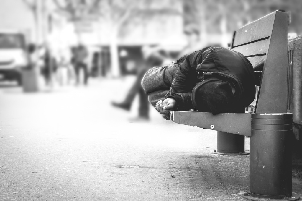poor homeless man or refugee sleeping on the wooden bench on the in picture id929671484 image
