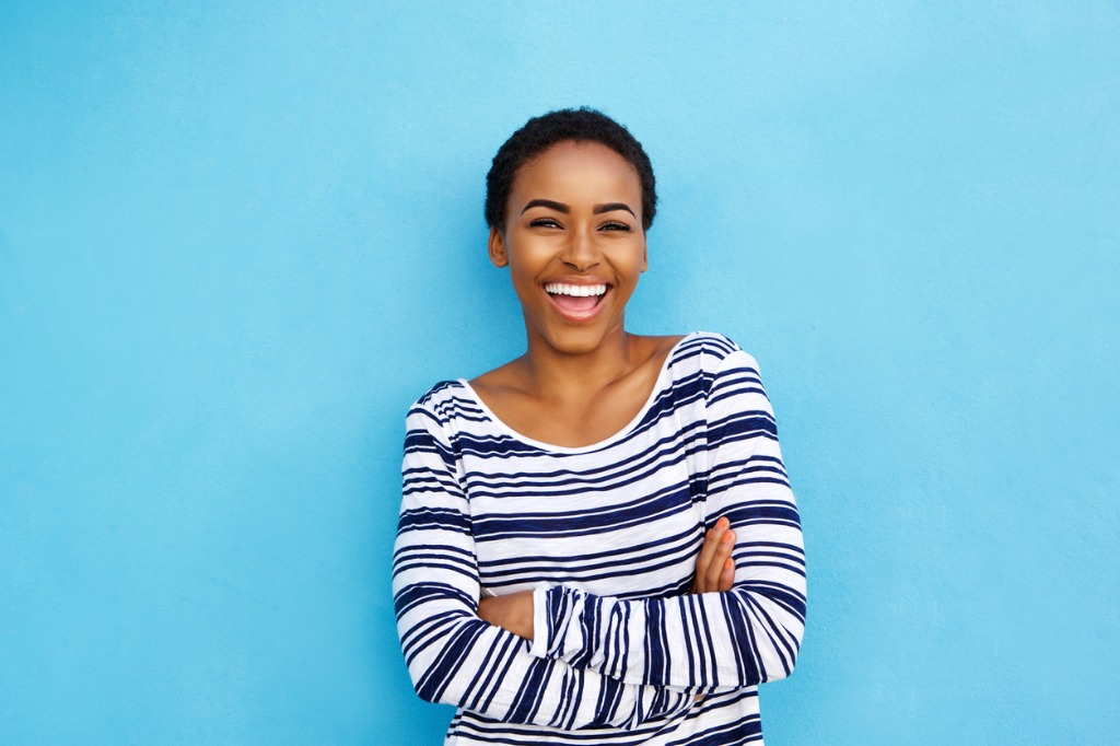 happy young black woman laughing against blue wall picture id857924506 image