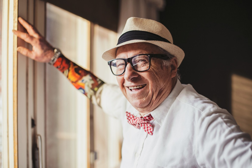 senior man with tattoo smiling and looking at camera picture id535295995 image
