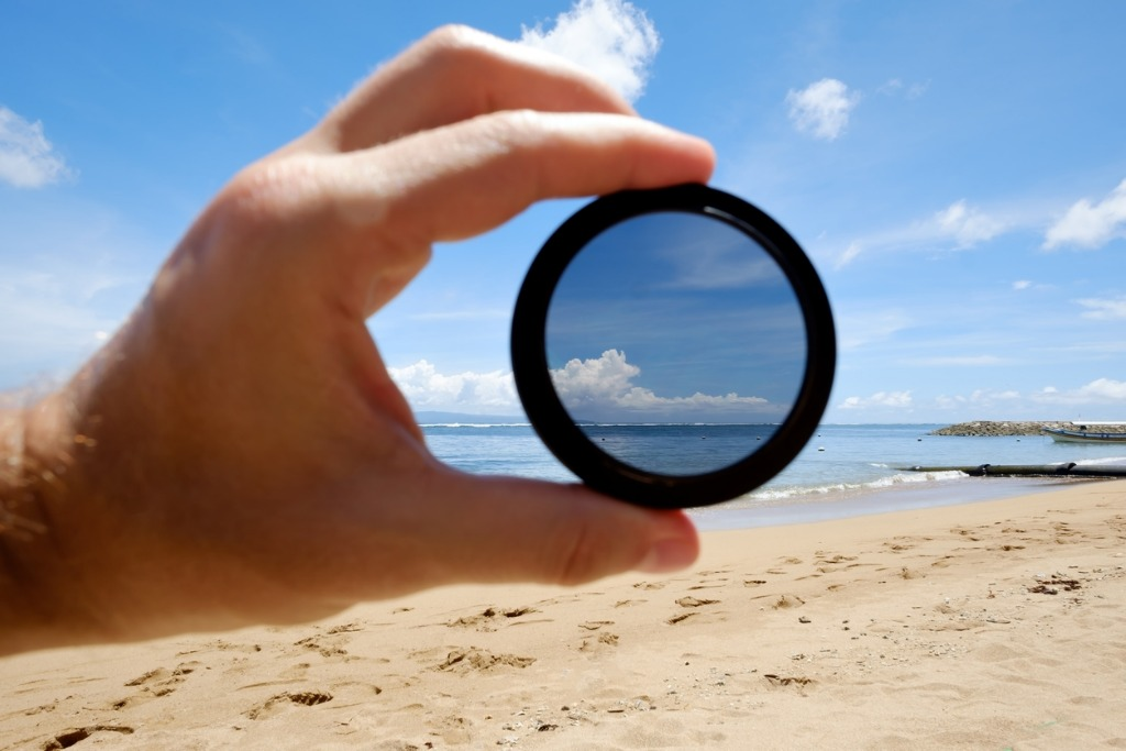 polarizing filter hold against the beach giving clarity picture id912435212