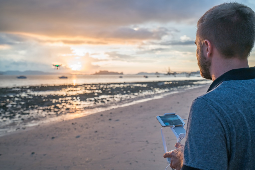 young man piloting a drone on tropical beach at sunset picture id691619790 image