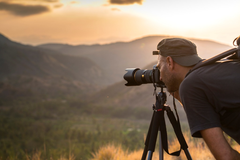 landscape male photographer in action taking picture picture id531321011 image