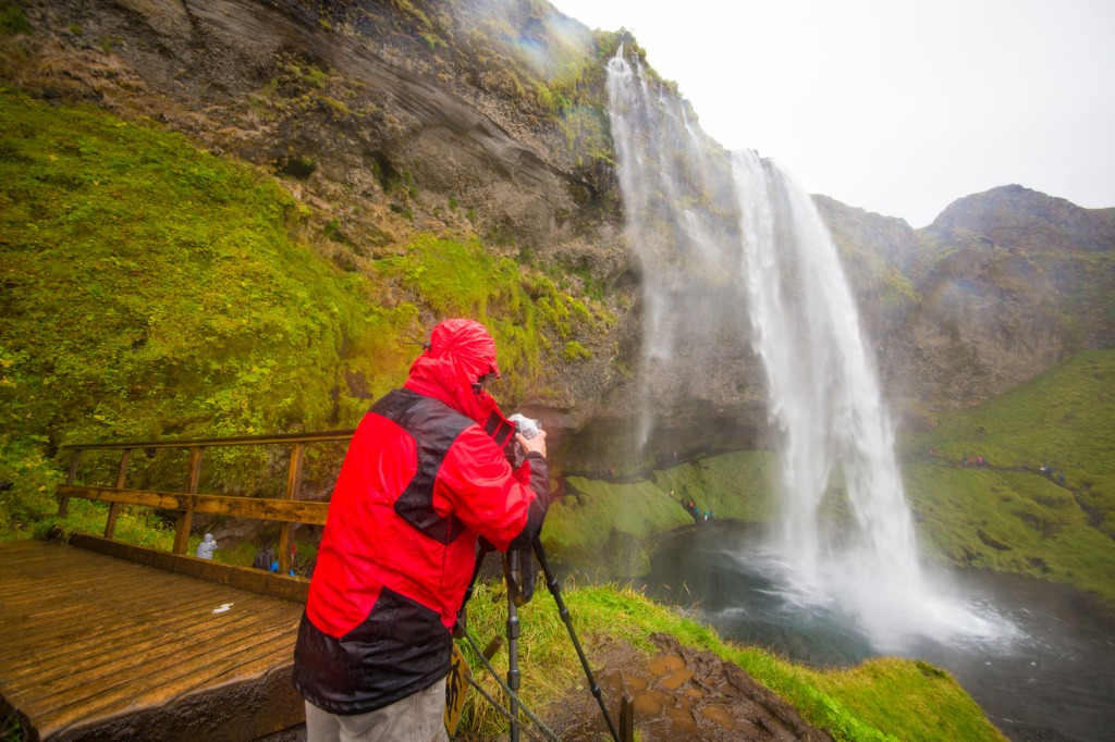 adventurous landscape photographer at waterfall photographing natural picture id918142620 image