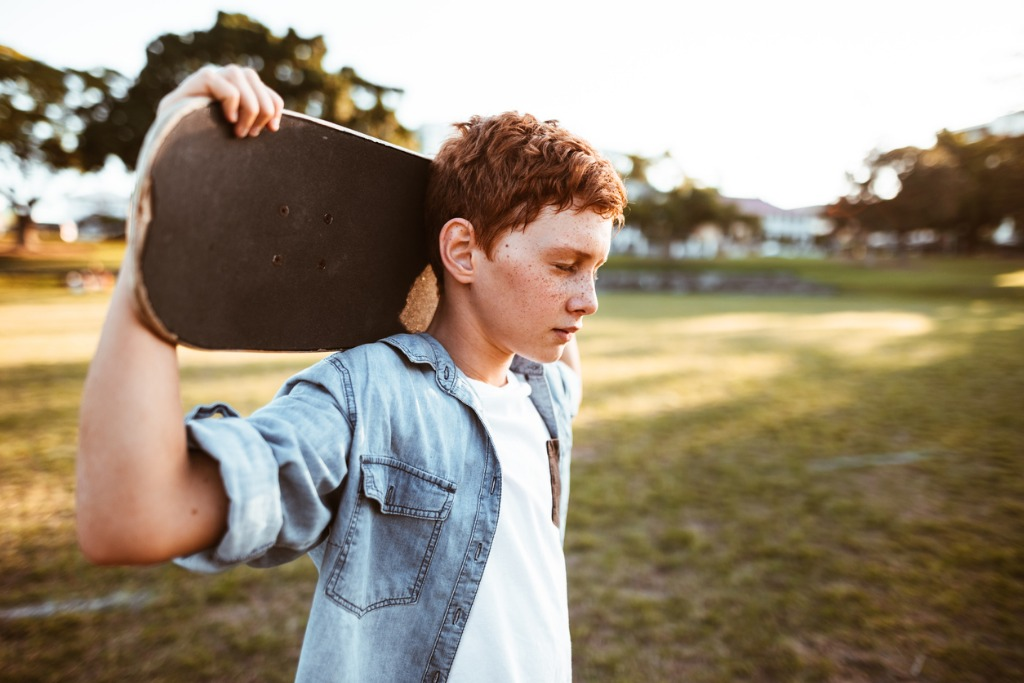sad kid with the skateboard on the shoulder picture id888369194 image