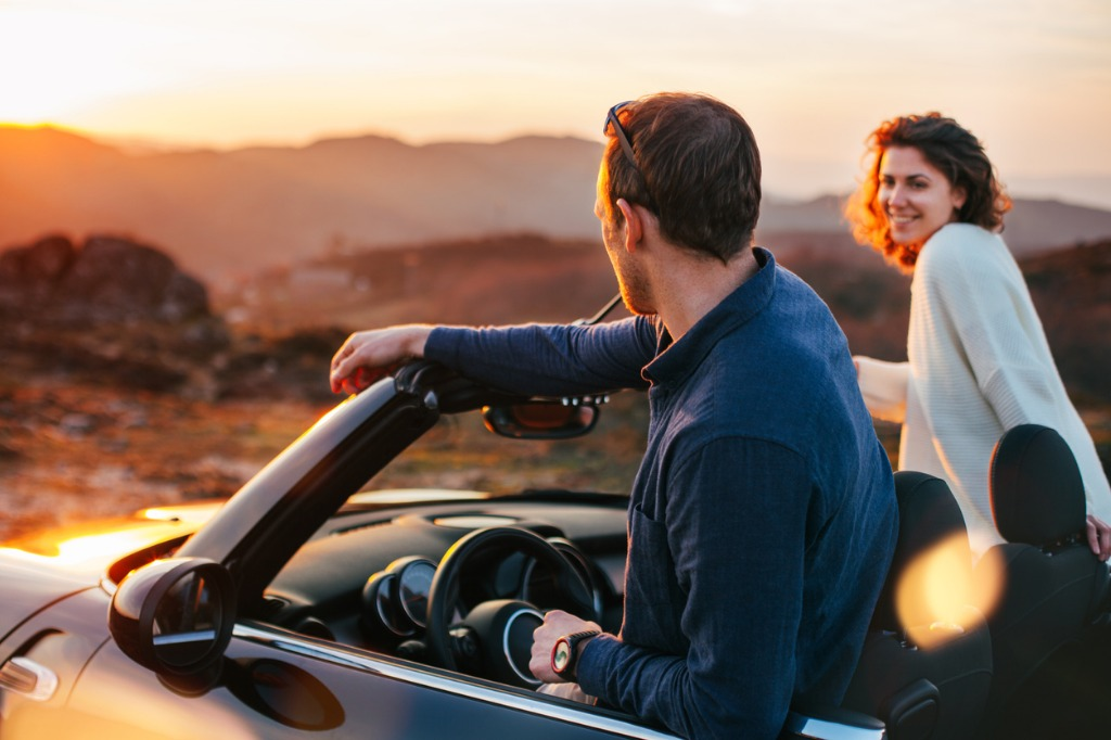 happy couple looking at sunset from convertible picture id842605642 image