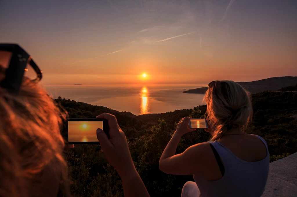 two women photographed with a smartphone fishing boat in the sunset picture id869591220 image