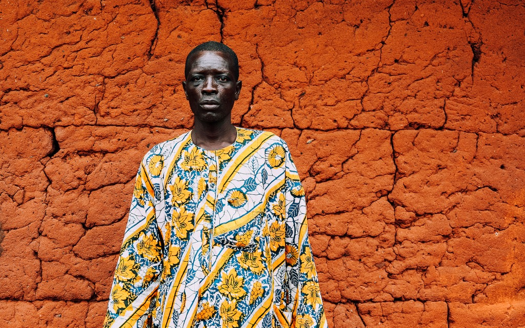 west african senior in front of mud hut picture id679951332 image