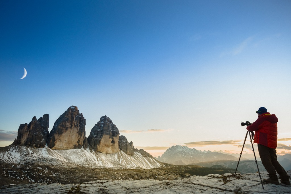 man photographs the moon above mountains landscape picture id857586812 image