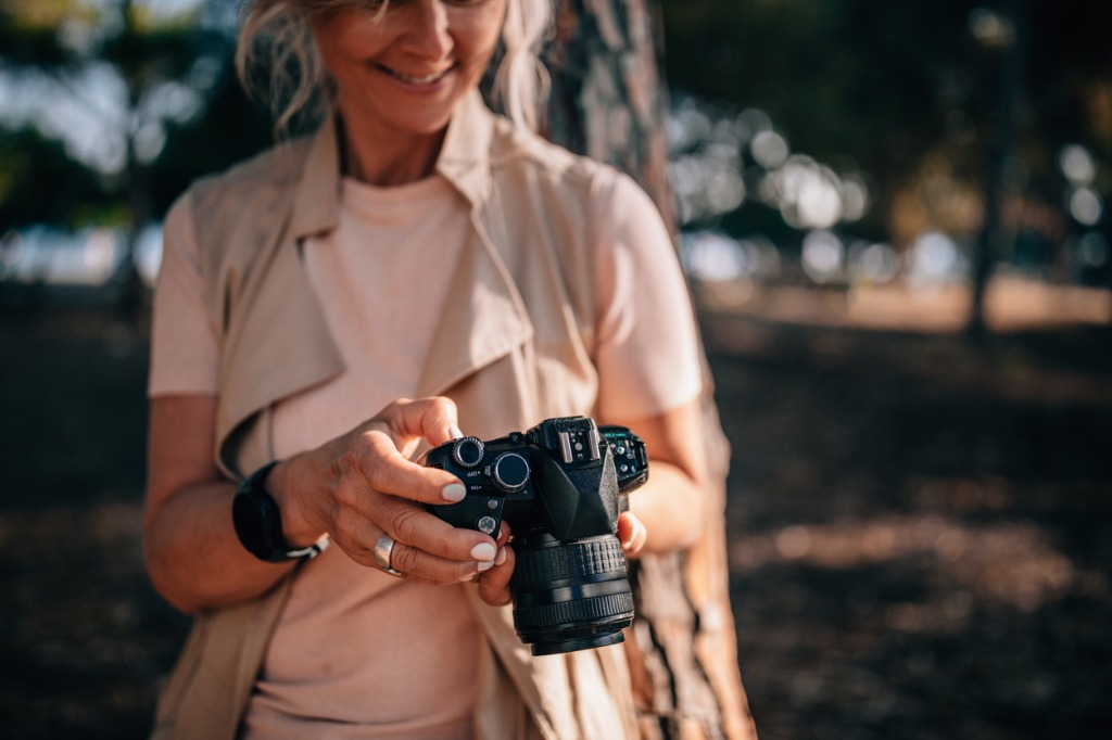 senior woman using camera and looking at photos in nature picture id979294778 image