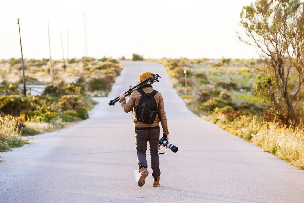 young photographer walking on desert road with tripod on his shoulder picture id696578902 image