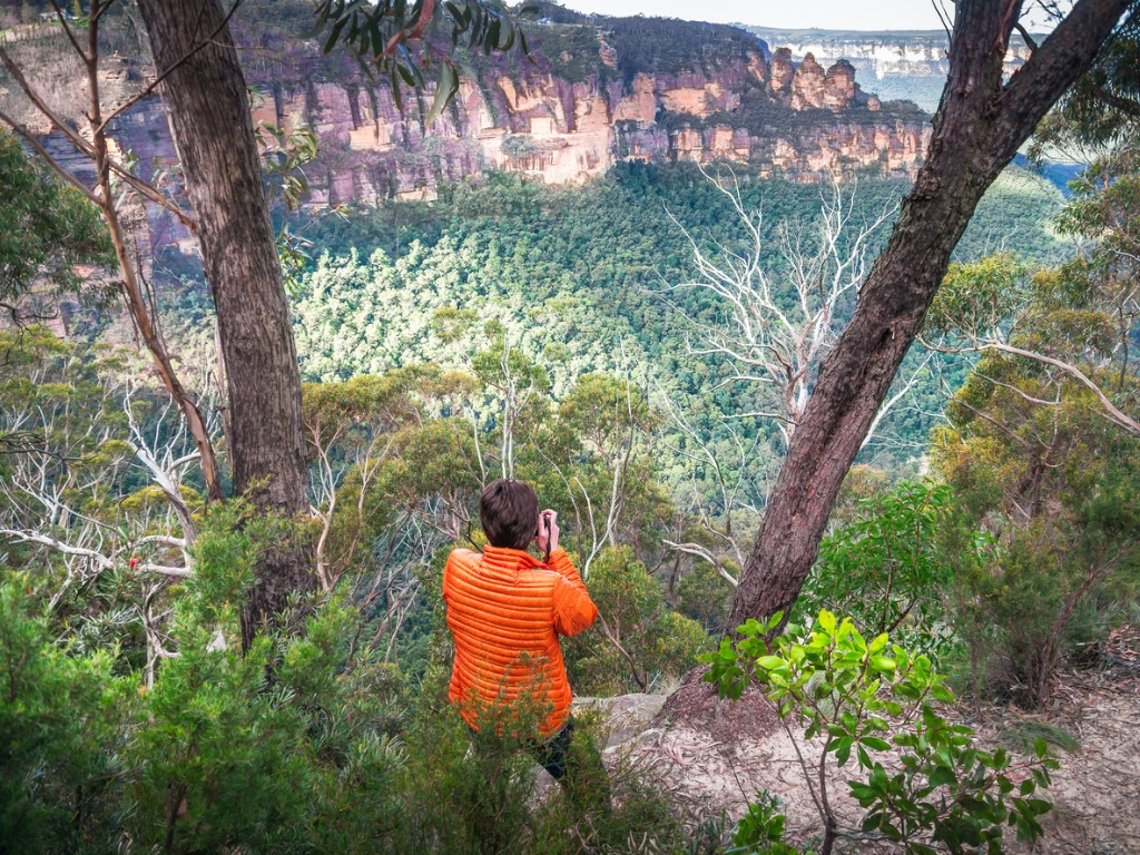 tourist finds a vantage point to photograph the three sisters in blue picture id939558392 image