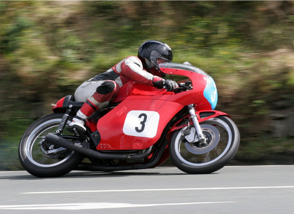 racer on a red motorcycle with matching gear on the road picture id172143818 image