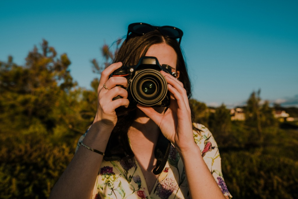 young woman taking a picture with a dslr camera picture id947527234 image