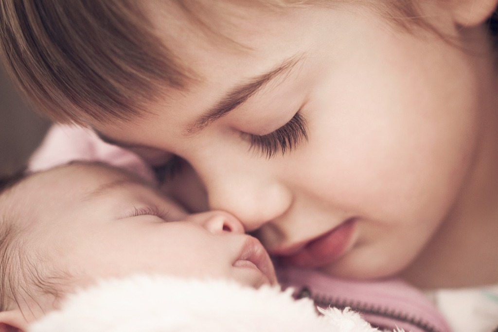 little girl looking at a newborn baby picture id176434134 image