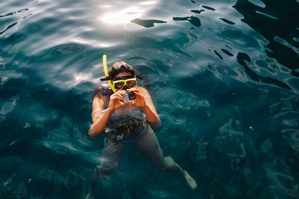 young woman setting up her action camera for snorkeling picture id1043930660 image
