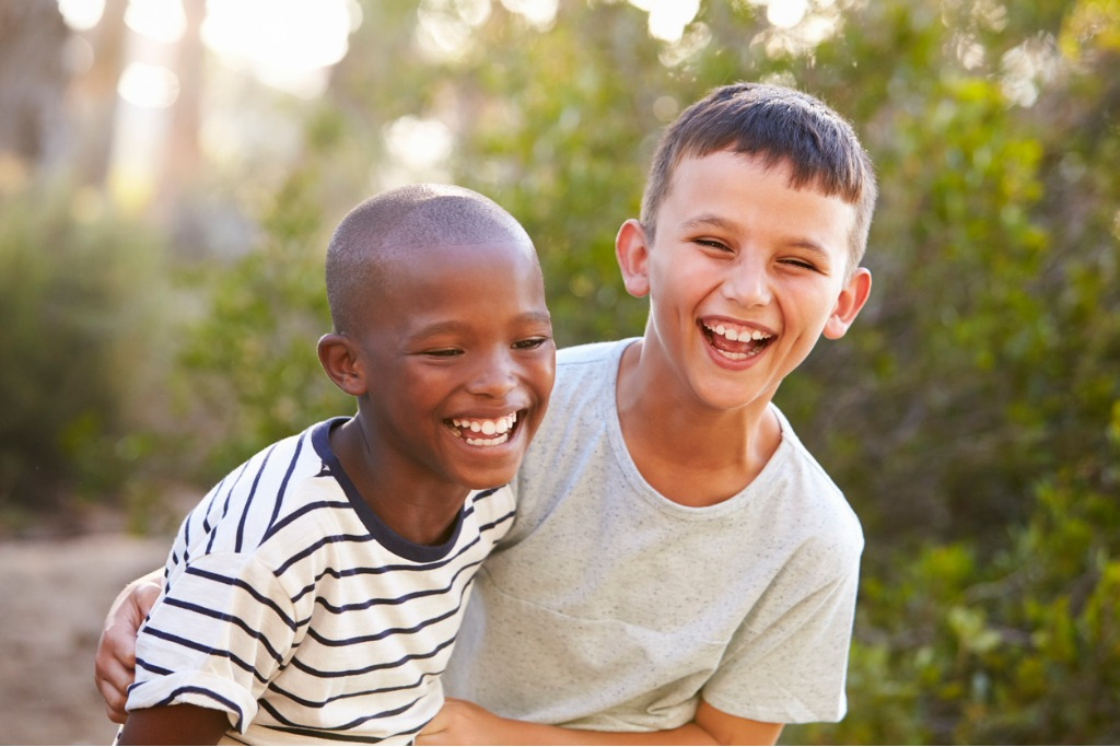 portrait of two boys embracing and laughing hard outdoors picture id829618546 image