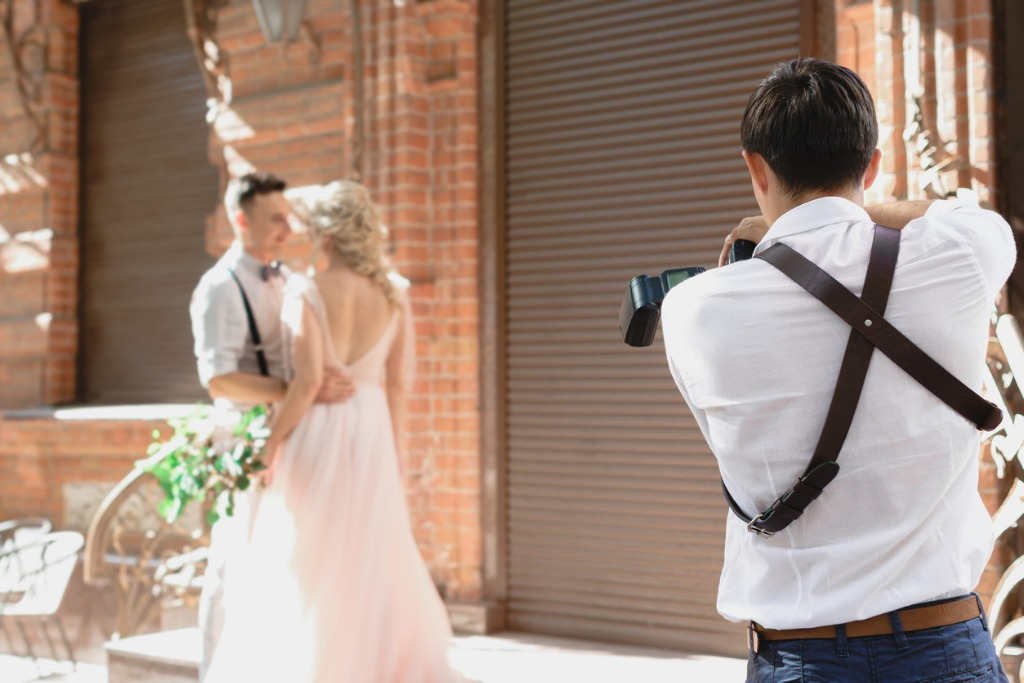 wedding photographer takes pictures of bride and groom picture id1056678658 image