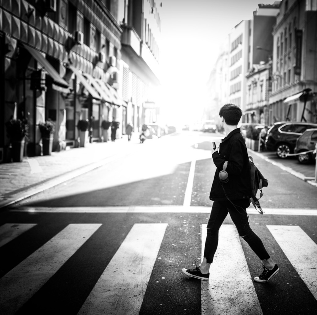 young man crossing a city street picture id864505578 image